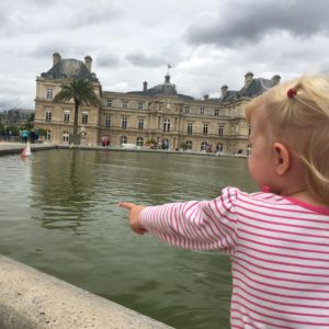 "Cecilia playing with the toy wooden sailboats at the Luxembourg Gardens. Nathan and I had seen a little French toddler exclaim delightedly over his ""bateau"" here fifteen years ago, when we were first married. Bringing our own toddler here was a dream come true!"